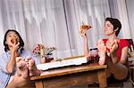 Female friends enjoying takeaway pizza