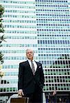 Homme d'affaires avec mallette en face du bâtiment en verre