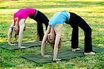 Two women bending over backwards on yoga mats outdoors