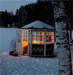 Gazebo with light inside in snowy landscape