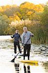 Deux personnes souriantes sur planches de pagayer sur la rivière