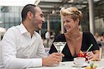 Souriant couple ayant des boissons en plein air
