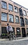 Businessman pushing bicycle outdoors