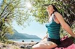 Smiling woman sitting by rural lake