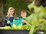 Children holding watering can in garden