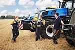 Farmers talking by machinery in field