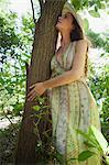 Jeune femme appuyé contre l'arbre