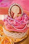 Un petit gâteau décoré de crème au beurre et d'un pendentif de Marie Antoinette