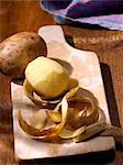 Pommes de terre, entières et pelées sur une planche de bois