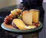 Assortiment de fromage avec des raisins sur planche en bambou