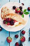 Une crêpe avec crème à la vanille, les cerises et les fraises