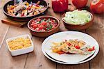 Fajitas de poulet sur une assiette ; Garnitures en arrière-plan