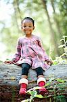 Girl sitting on log in park, Johannesburg, South Africa
