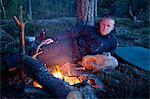Homme couché en camping dans la forêt