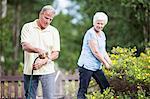 Senior woman looking at man watering plants in garden