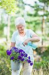 Happy senior woman spraying water on flower plant