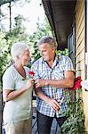 Senior man giving rose to woman at garden
