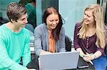 Drei glückliche Freunde über Laptop am Kaffeetisch