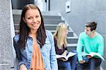 Porträt einer glückliche Studentin mit Freunden studieren auf Schritte im Hintergrund