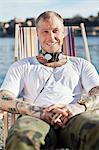 Porträt eines tätowierten Mannes mit Kopfhörern sitzen im Liegestuhl am Strand