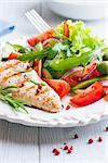 Gegrilltes Hähnchenfilet mit mediterraner Salat auf einem Teller