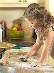 Mädchen Ausschneiden von Cookies in Küche
