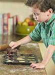 Junge löffelt Teig in Pfanne in Küche