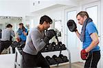 Boxer pratiquer avec formateur dans la salle de gym