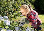 Femme odeur de fleurs dans le jardin