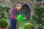 Femme arroser les plantes dans le jardin