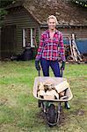 Woman pushing firewood in wheelbarrow