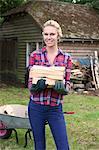 Woman carrying firewood in backyard