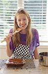 Girl tasting cake frosting in kitchen