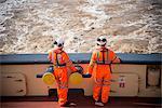Workers on tug boat overlooking ocean