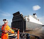 Travailleur sur bateau remorqueur donnant sur navire