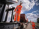 Railway workers standing on train
