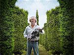 Man holding hedge trimmer in garden