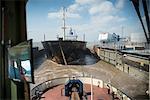 Remorqueur tirant sur le navire dans le port urbain