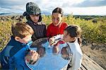 Family examining metal sundial