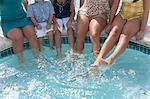 Family dangling feet in swimming pool