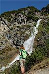 Frau Wandern und genießen die Aussicht mit Wasserfall