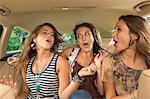 Three girls in back seat of car