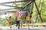 Group of friends running on bridge holding american flag