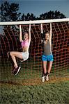 Girls hanging from soccer goal