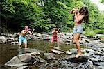 Two young men splashing female friend in river