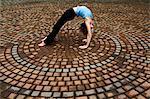 Woman bending backwards in paving stone circles