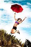 Teenage girl jumping with umbrella