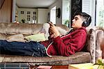 Teenage boy on sofa, listening to music