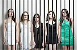 Portrait de cinq jeunes femmes debout côte à côte fesses prison bars