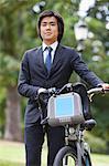 Jeune homme d'affaires ayant qualité pour agir au parc de vélo